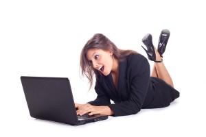 Junge Frau ist überrascht vor ihrem Laptop